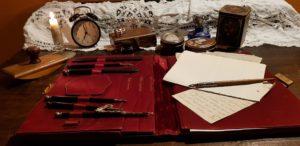antica cartellina con penne e fogli, suppellettili varie